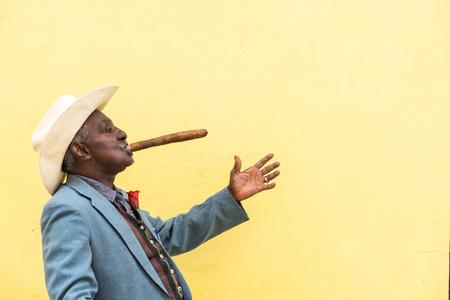 하바나, 쿠바 - 9 월 (27), 2015 : 쿠바, 하바나에서 노란색 벽 배경에 큰 쿠바 시가 흡연 동안 전통적인 쿠바 사람이 사진을 위해 포즈.