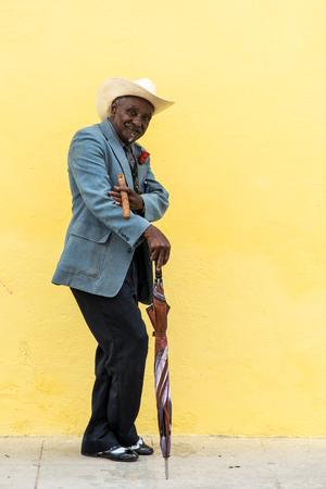 Havana, Cuba - September 27, 2015: Traditional Cuban man posing for photos while smoking big cuban cigar on yellow wall background in Havana, Cuba.