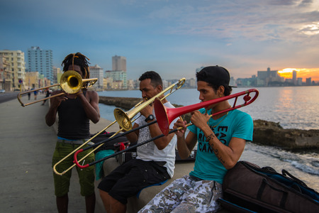 play popular: Havana, Cuba - September 25, 2015: Group of friends play music at sunset at Malecon,  most popular and famous sea front promenade in Havana, Cuba. Music is very common hobby in Cuba but also way to earn extra cash. Editorial