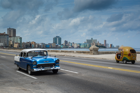 cuba flag: Havana, Cuba - September 28, 2015: Classic american car drive  on Malecon sea front promenade in Havana,Cuba. Classic American cars are typical landmark and tourist attraction for whole Cuban island.
