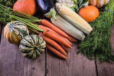 comiendo fruta: El mercado de oto�o verduras frescas y flores en la mesa de madera Foto de archivo