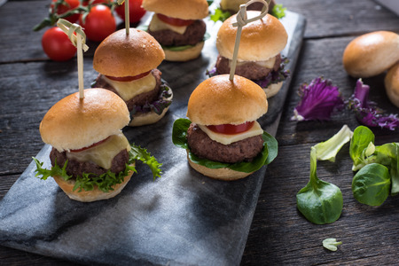 hamburguesa: mini hamburguesas de carne, alimento del partido en mesa de madera