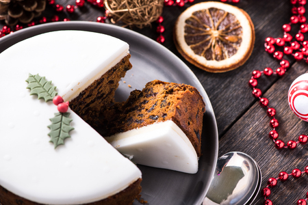cakes and pastries: Christmas fruit cake on wooden table with festive decorations