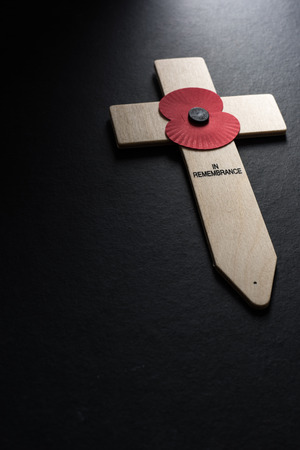 Remembrance Day poppy symbol on wooden cross, black background