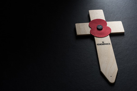 Remembrance Day poppy symbol on wooden cross, black background
