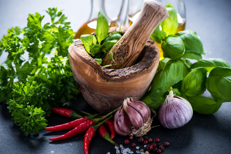 Fresh herbs and spices in wooden mortar, cooking concept Stockfoto
