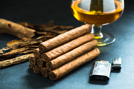 cigar: pile of authentic cuban cigars, tobacco leafs in background