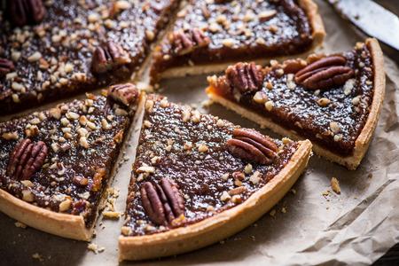 pecan pie: slicing pecan pie on wooden table, overhead view