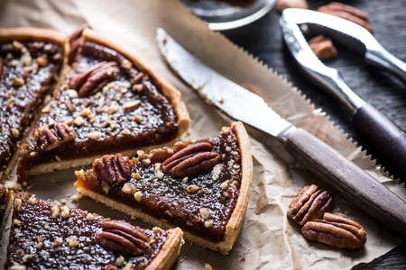 slicing pecan pie on wooden table, overhead view