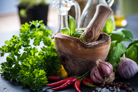 food plant: Fresh herbs and spices in wooden mortar, cooking concept Stock Photo