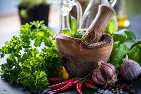 Verse kruiden en specerijen in houten mortier, koken begrip Stockfoto