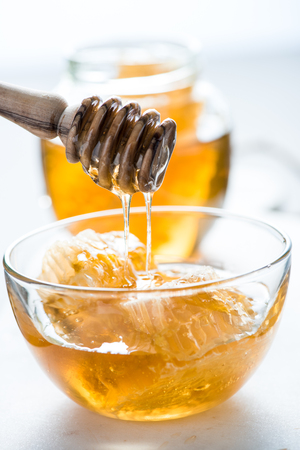 honey comb: wooden honey drizzler and honey comb, white background