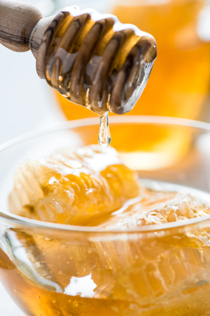 drizzler: Dripping honey into jar from wooden drizzler