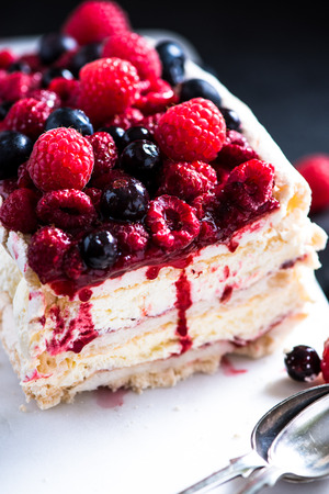 custard flavor: Homemade Pavlova with berry fruits on serving board, from above