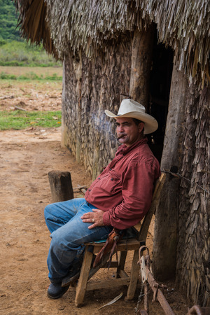 pinar: Vinales Valley, Cuba - September 24, 2015:  Local cuban coutryside man smoke cigar in front of village house in scenic landscape of Vinales Valley,Cuba.