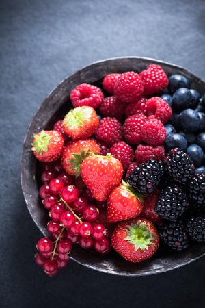 Fresh berries in rustic bowl, antioxidant concept