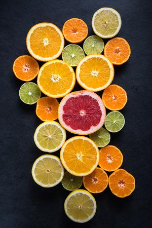 mandarin orange: Citrus half cut fruits on dark background, from above