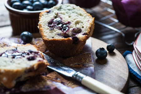 blueberry muffin: Fresh homemade blueberry muffin, cut in half with vintage knife on rustic table