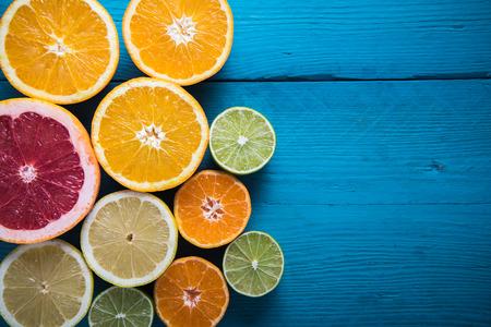 fresh citrus half cut fruits overhead on wooden table