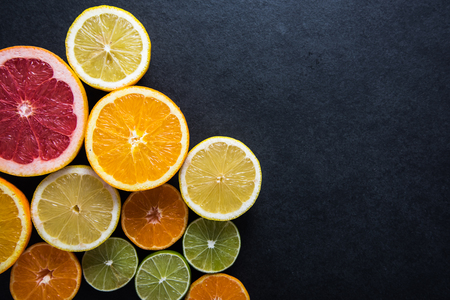 copy space: Fresh citrus fruits half cut, dark border background with copy space,from above