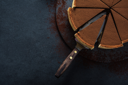 Sliced chocolate tort on dark background, overhead view Stock Photo