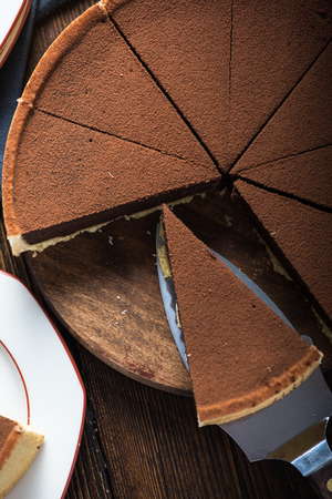 tort: Portion of chocolate tort or cake on plate on wooden table Stock Photo