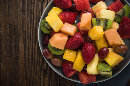 fruity salad: Plate full of healthy exotic fruits slices, from above on wooden table