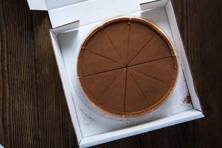 porcion de pastel: El chocolate y el cacao torta en la caja de transporte, desde arriba sobre la mesa de madera
