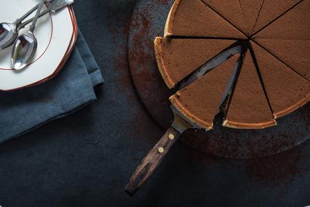 tort: Sliced chocolate tort on dark background, overhead view Stock Photo