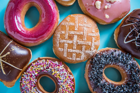 dozen: Dozen of artisan donuts overhead view on bright blue pastel background