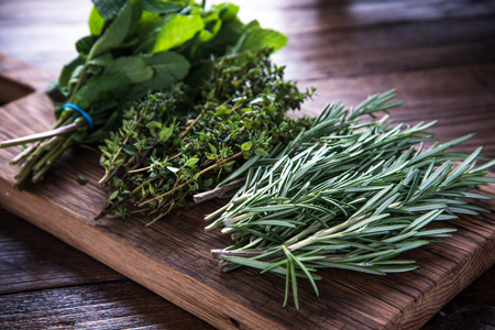 kitchen garden: bunch of garden fresh herbs on wooden board from above