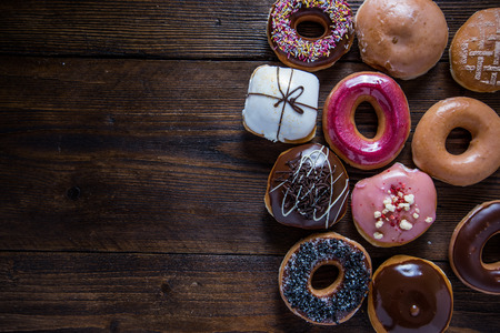 Sweet and vbrant donuts on wooden table, overhead with copy space Foto de archivo