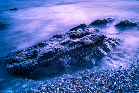 slow motion: Slow motion waves on rocky beach at sunset Stock Photo