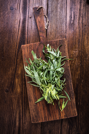 tarragon: Fresh tarragon on wooden board