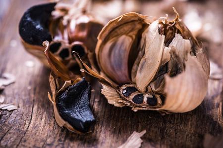 balsamic: Whole balsamic black garlic on wooden board