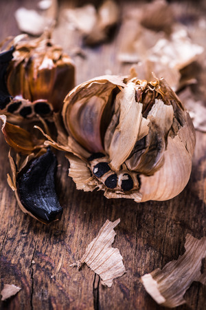 Whole balsamic black garlic on wooden board
