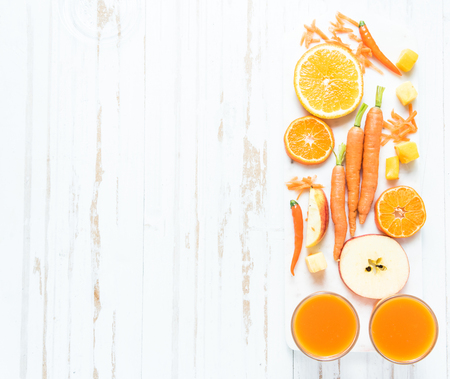 Recipe for orange , carrot and apple smoothie on wooden table