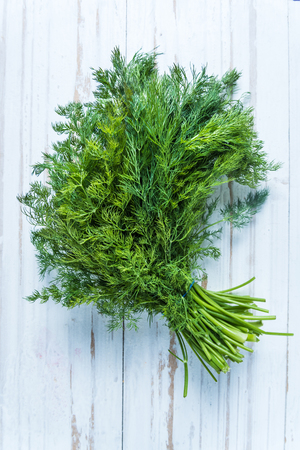 dill: Fresh dill from garden on wooden table, lay flat vie from above