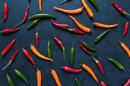 cayenne pepper: Vibrant peppers on dark slate, lay flat from above Stock Photo