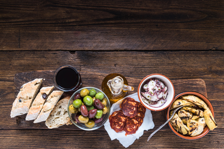 Wooden board with tapas, olives and salami and olive oil, from above, copy space for text or advert.