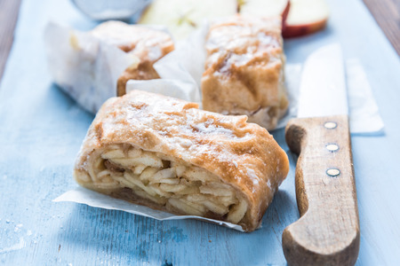 home baking: Home baking, apple strudel with ingredients on wooden table. Bright and vibrant pastel food portrait. Stock Photo