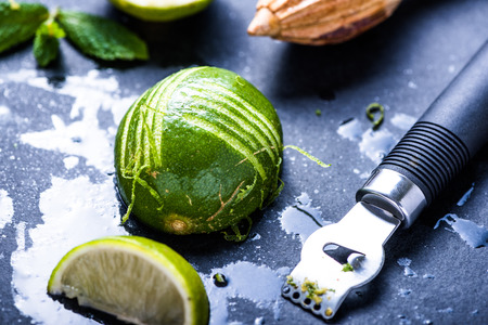 zesty: Lime and zest, natural refreshing ingredients on dark slate. Stock Photo