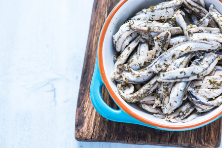 Anchovy with herbs in traditional tapas ceramic bowl, from overhead on wooden board