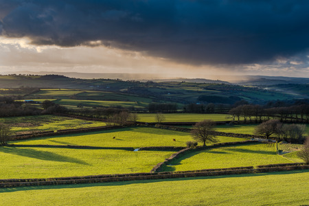 storm clouds: Farmland and coutryside with stormy clouds rolling with pouring rain at sunset. View from hill top, long shadows.
