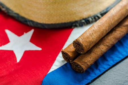 Traveling to Cuba concept background. National flag, straw hat and cigars.