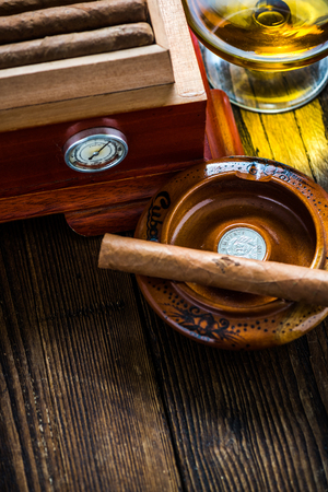 congratulating: Cigar with glass of cognac and humidor on wooden table. Rich person or congratulating concept.