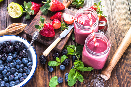 Preparation of antioxidant and refreshing smoothie, well being and weight loos concept. On wooden table from above. Stock Photo