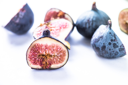 clean cut: Fresh organic fig cut in half with vibrant red seeds, diet and clean eating concept.