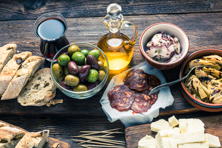 Tapas served in restaurant or bar on wooden table, with red wine meat and bread.