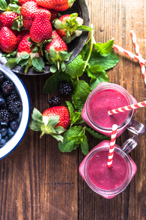 Making fresh dieting berry smoothie, ingredients and jar with vibrant straw, from above